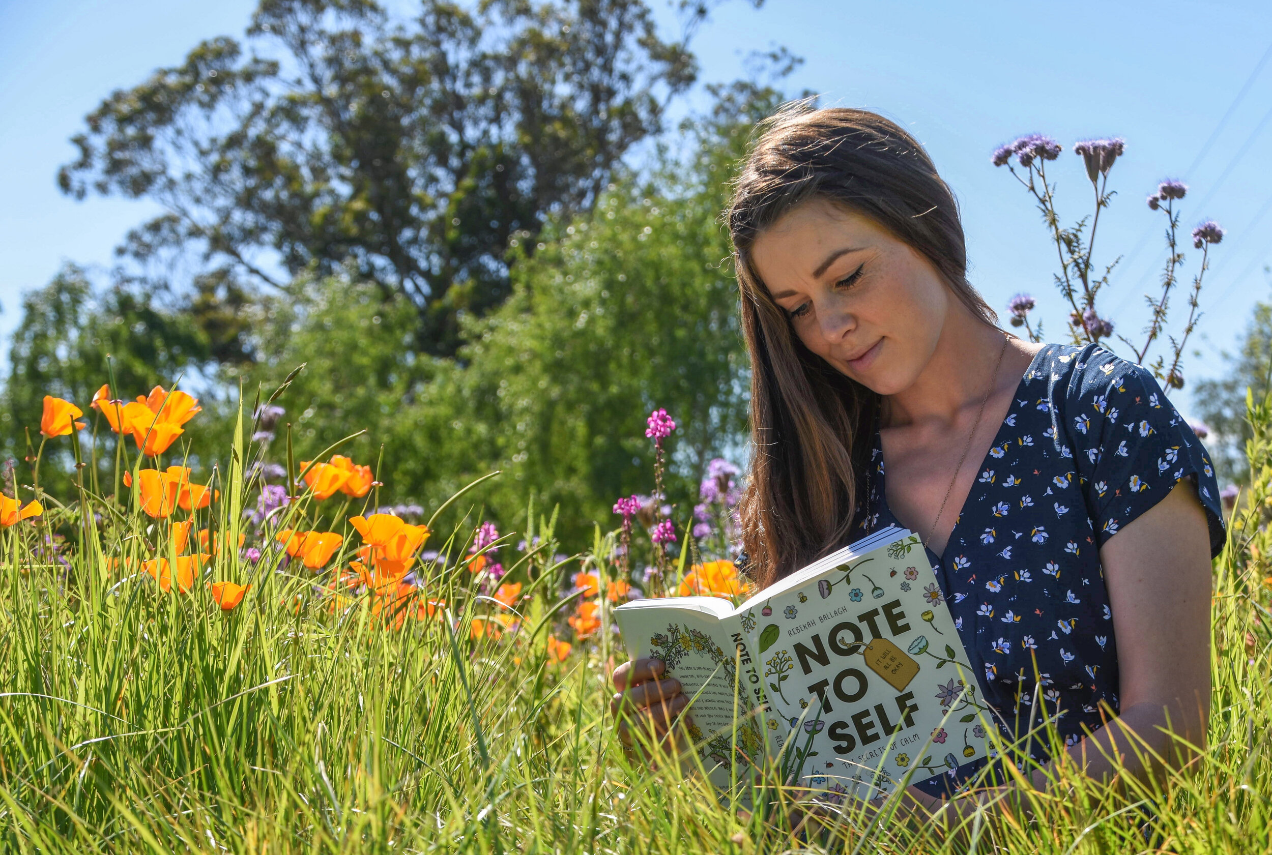 """Rebekah reading her book """"Note To Self"""" in a field of orange and purple flowers and grass"""