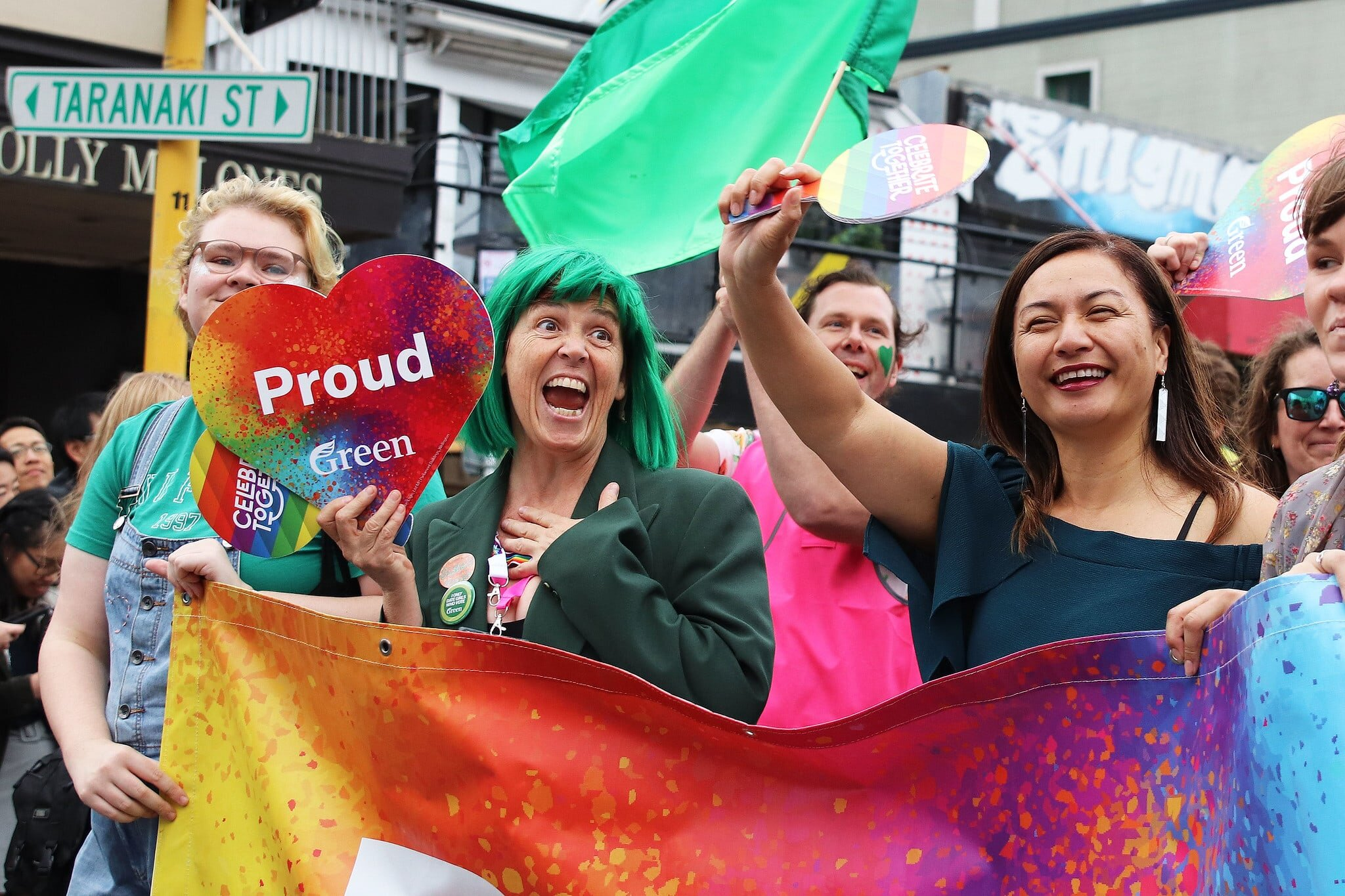 Jan in a green wig walking alongside Marama Davidson at the Pride Parade holding a rainbow heart that says: Proud Green, credit to: Newsroom.co.nz