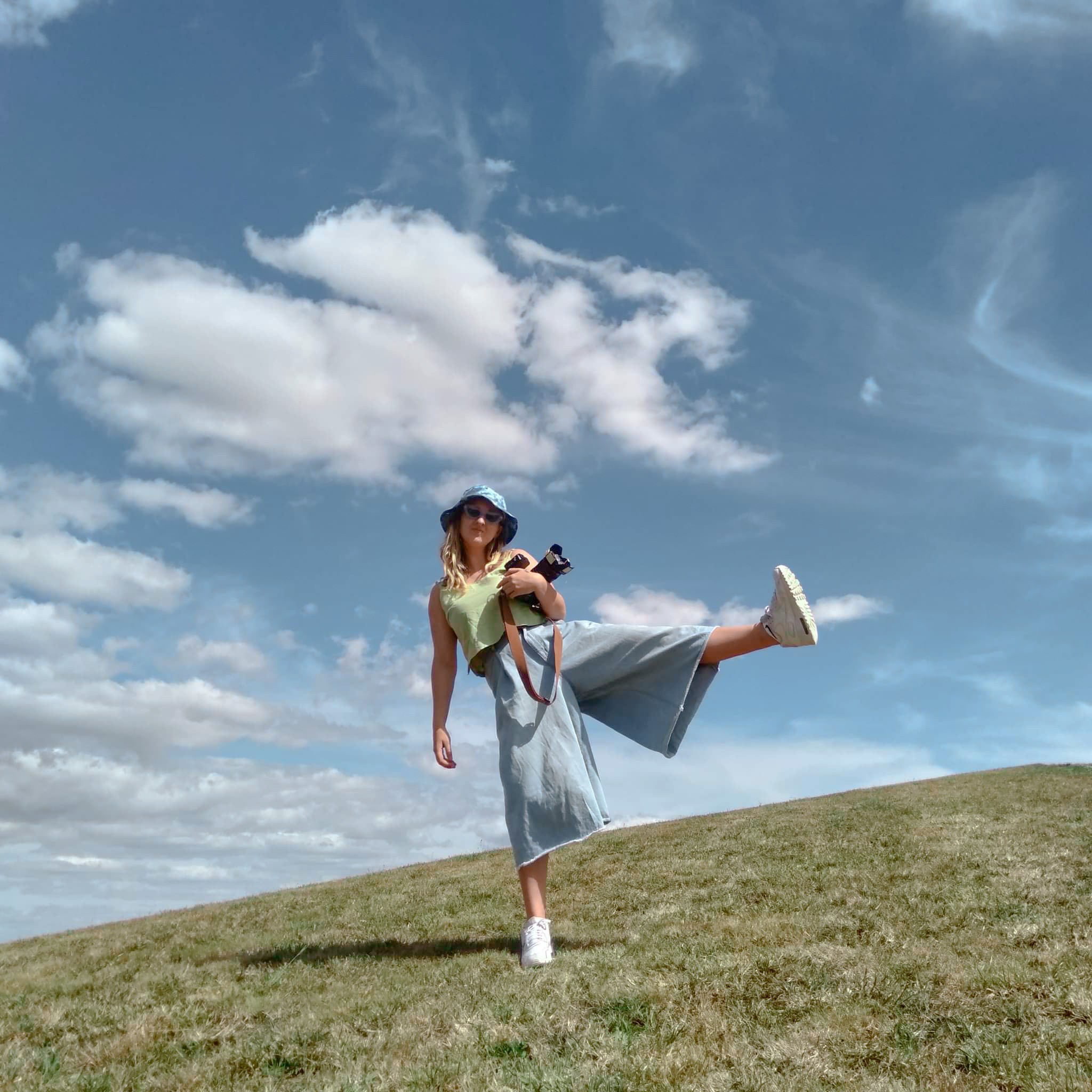 Beka on a green hill with blue sky at the back, standing on one foot with a camera in her hands