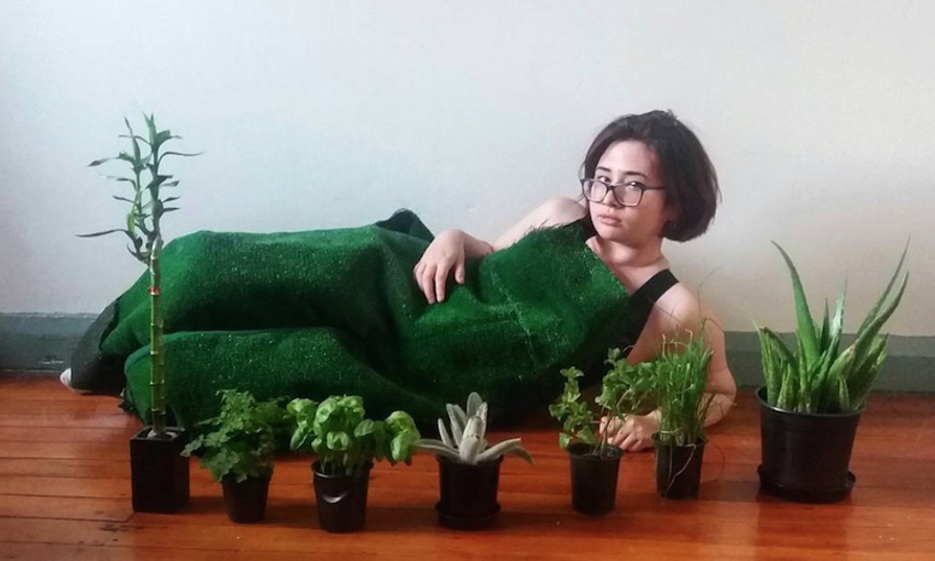 Vanessa in a green overalls lying on the wooden floor with a bunch of potted plants in front of her