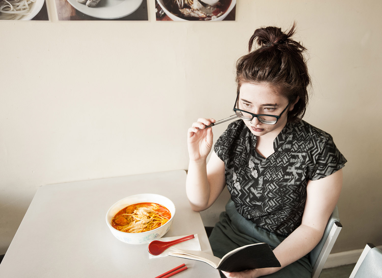 Vanessa with a bowl of laksa in front of her on the table and a very thoughtful look on her face