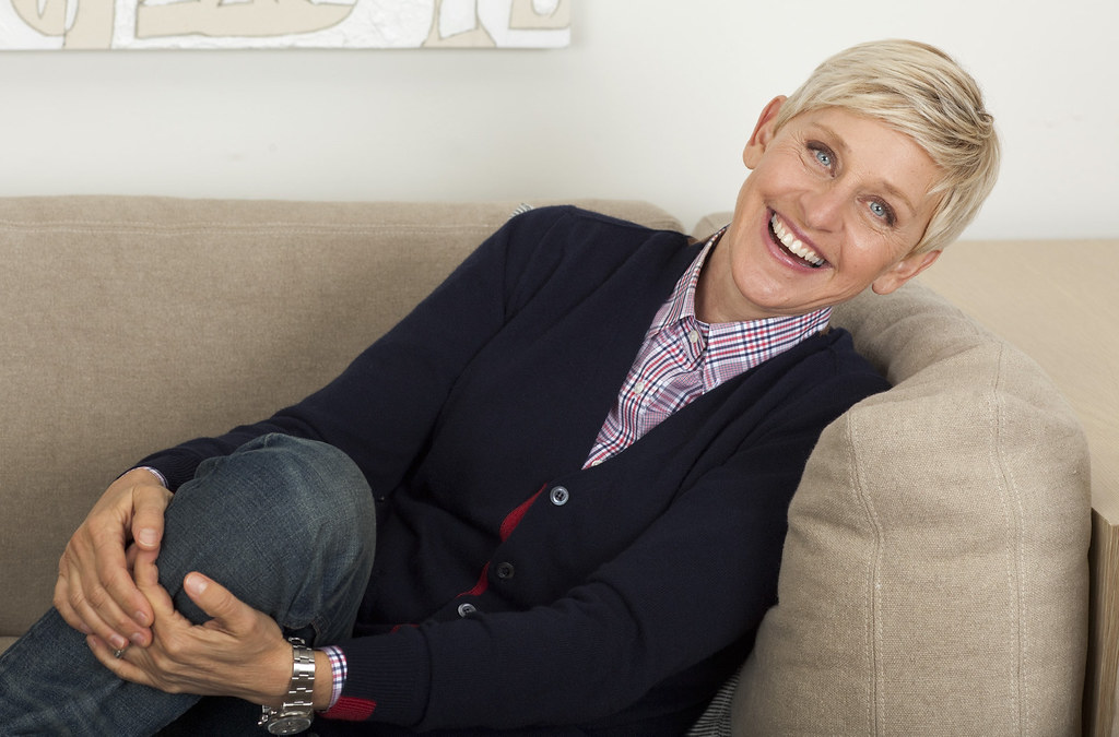 Ellen Degeneres is smiling, sitting on a couch