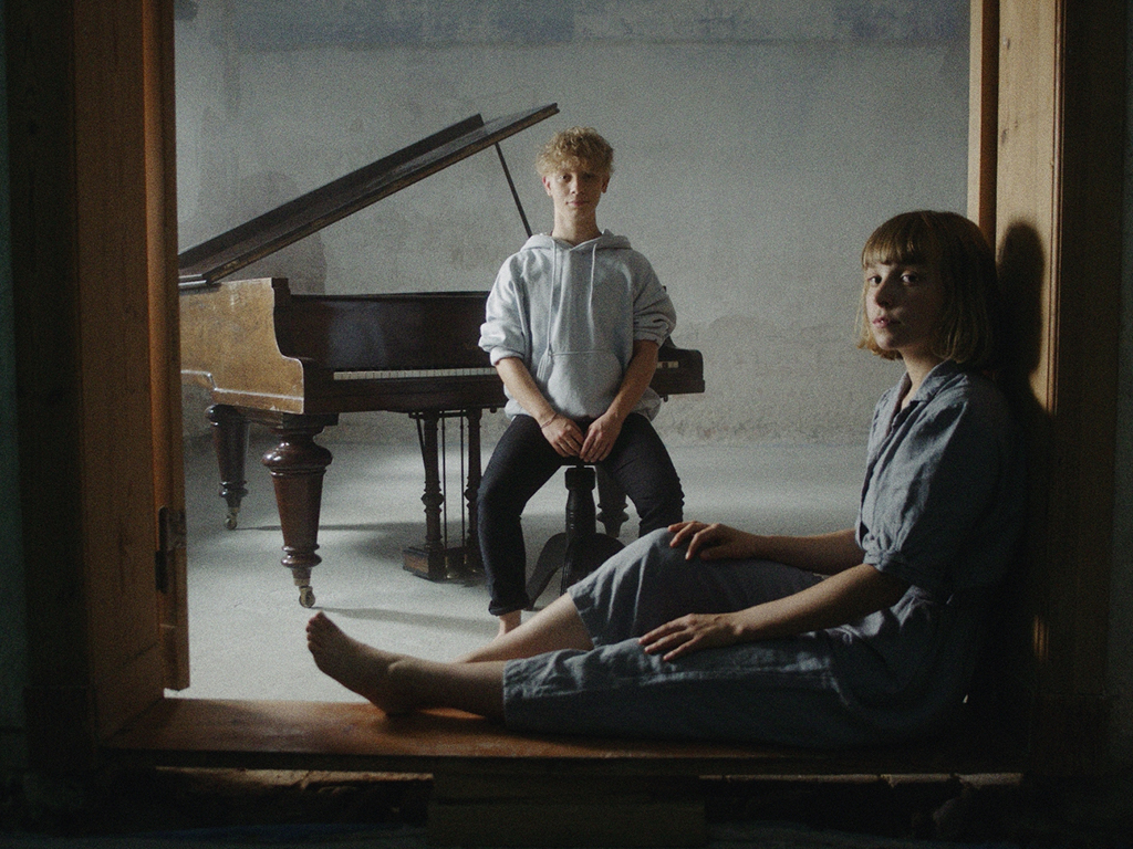Zwei Menschen sitzen an einem Flügel