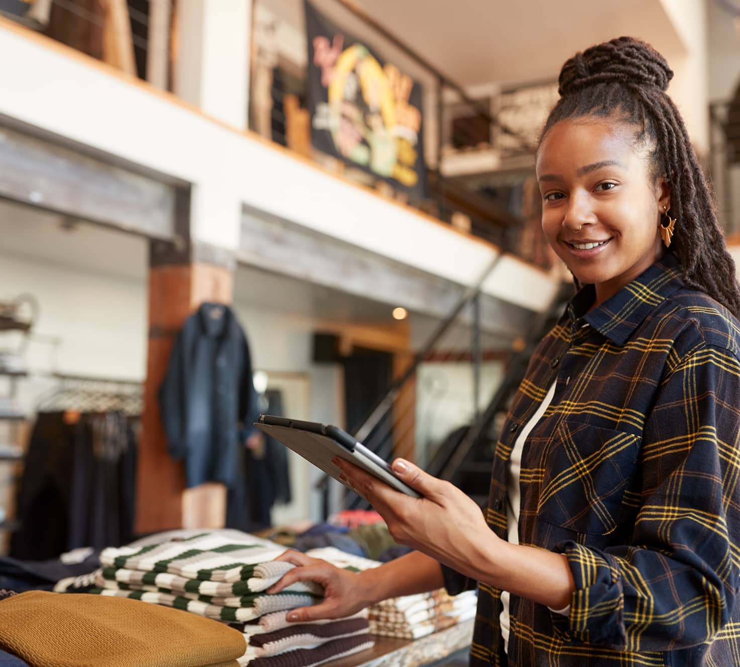 Woman Checking Stock In Retail Store With Tablet