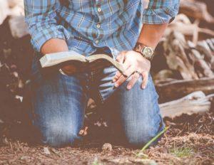 man kneeling and reading Bible in prayer