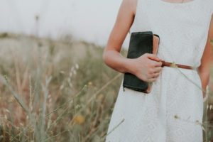 woman holding Bible in a field of wheat