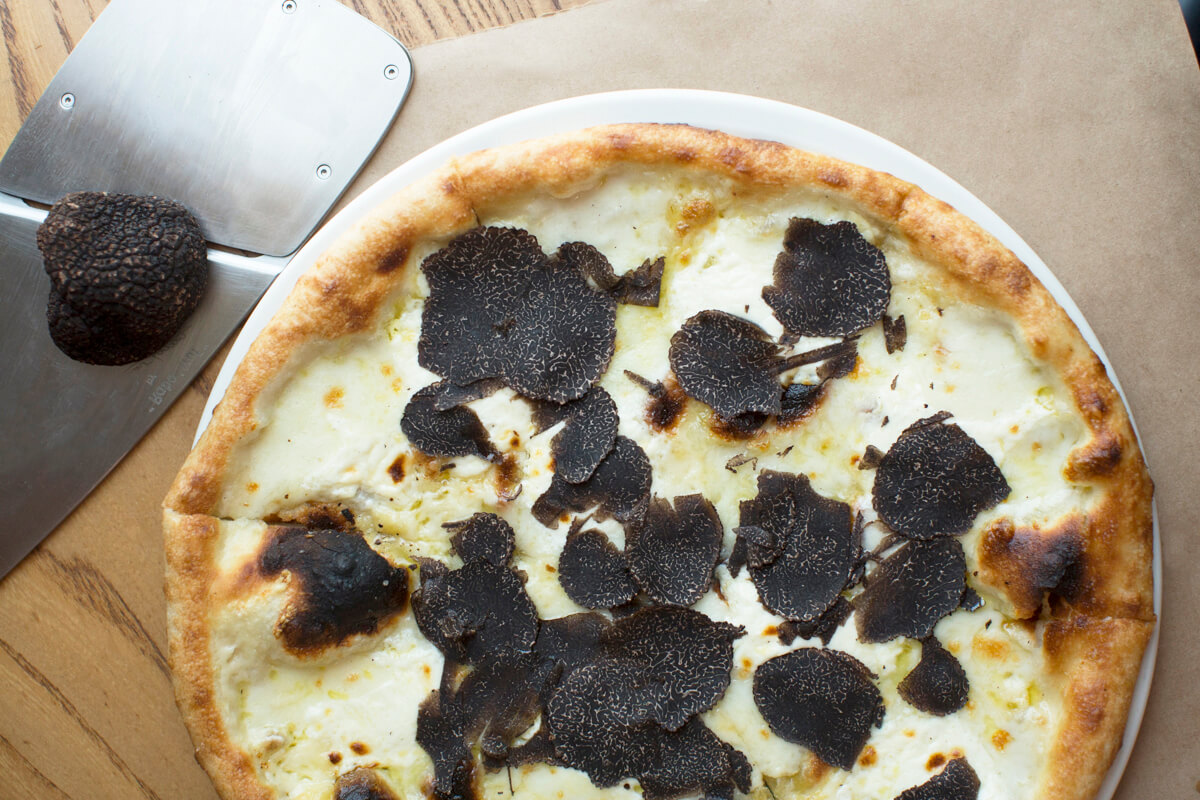 pizza covered in shaved black truffles