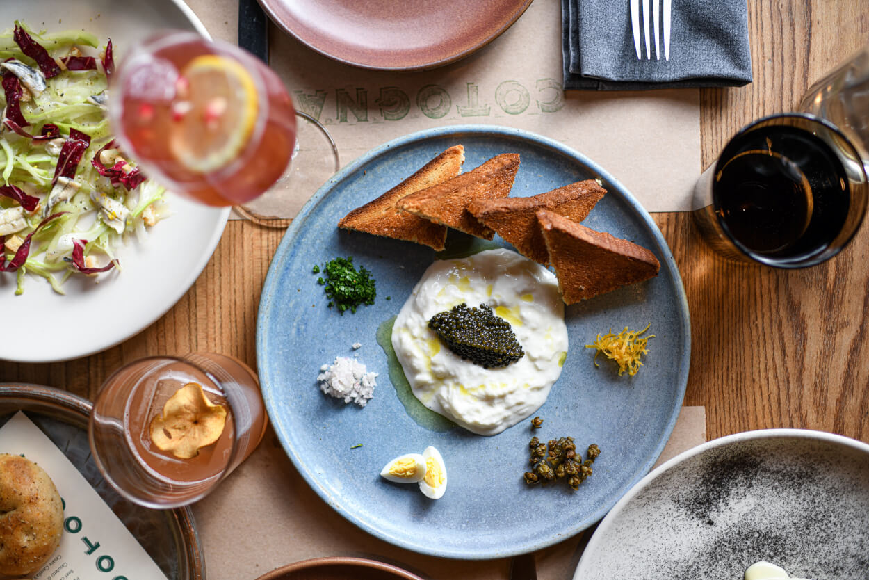 Plates of food and drinks, with a dish of burrata with caviar in the center