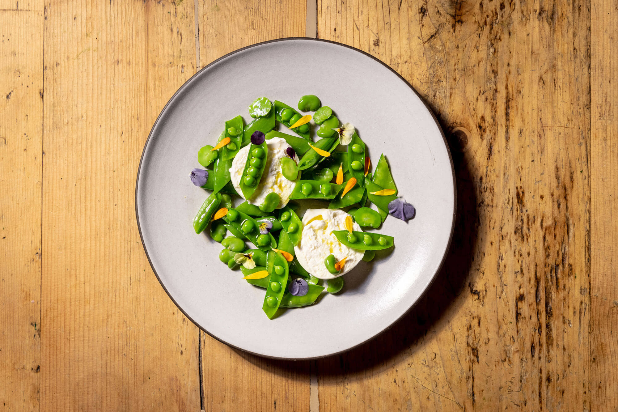A dish filled with fresh green peas, flowers and cheese
