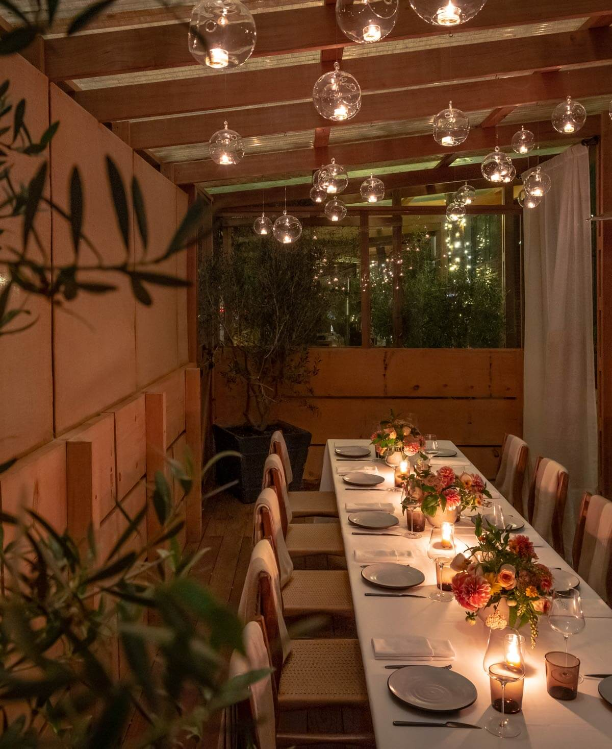 A set table in the outdoor dining space at night