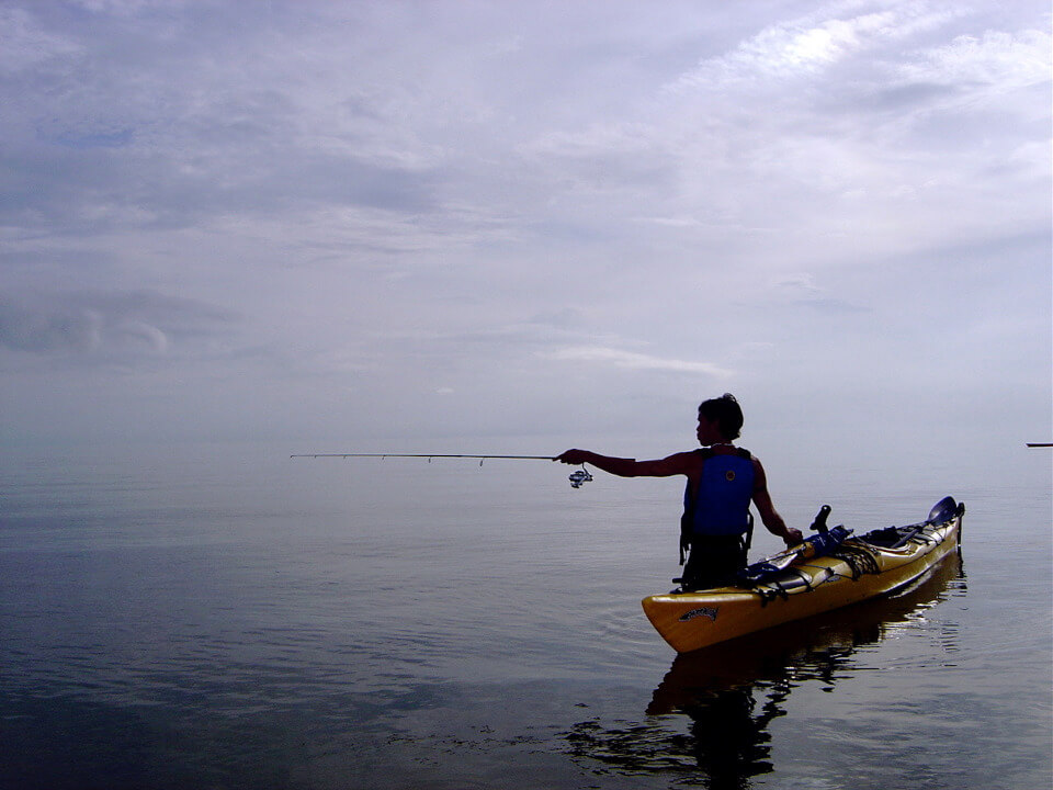 A lonely fisher with his kayak.