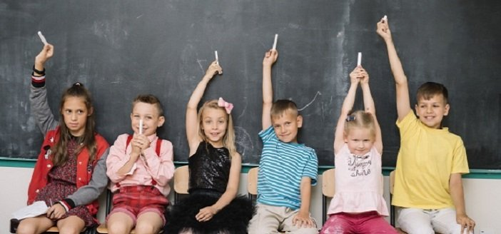 school children sitting in front of a blackboard, holding chalk above their heads