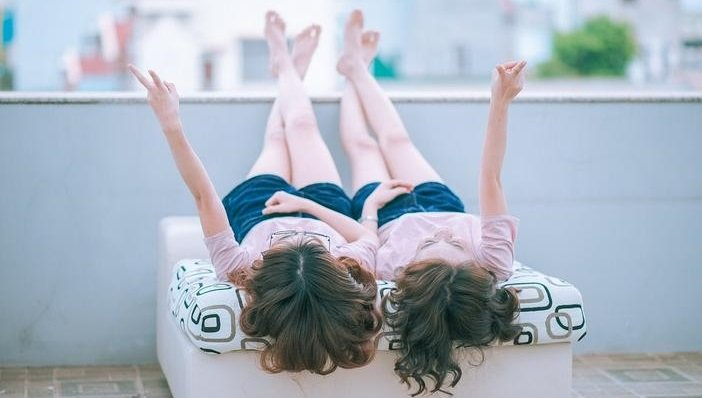 oblique angle of two girls lying on a chaise looking up at the sky holding up two finger peace signs.