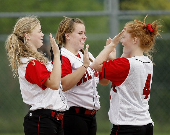 three teen girls in sports jerseys celebrating with high five hand claps.