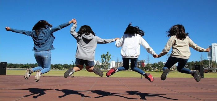 rear view of 4 teens holding hands and leaping into the air together with notable shadows in sunshine