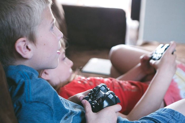 kids lying together on a sofa with game controllers playing video games.