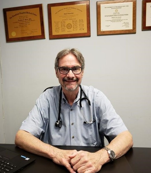 Medical Doctor Stephen Beck, MD, in office with degrees on wall