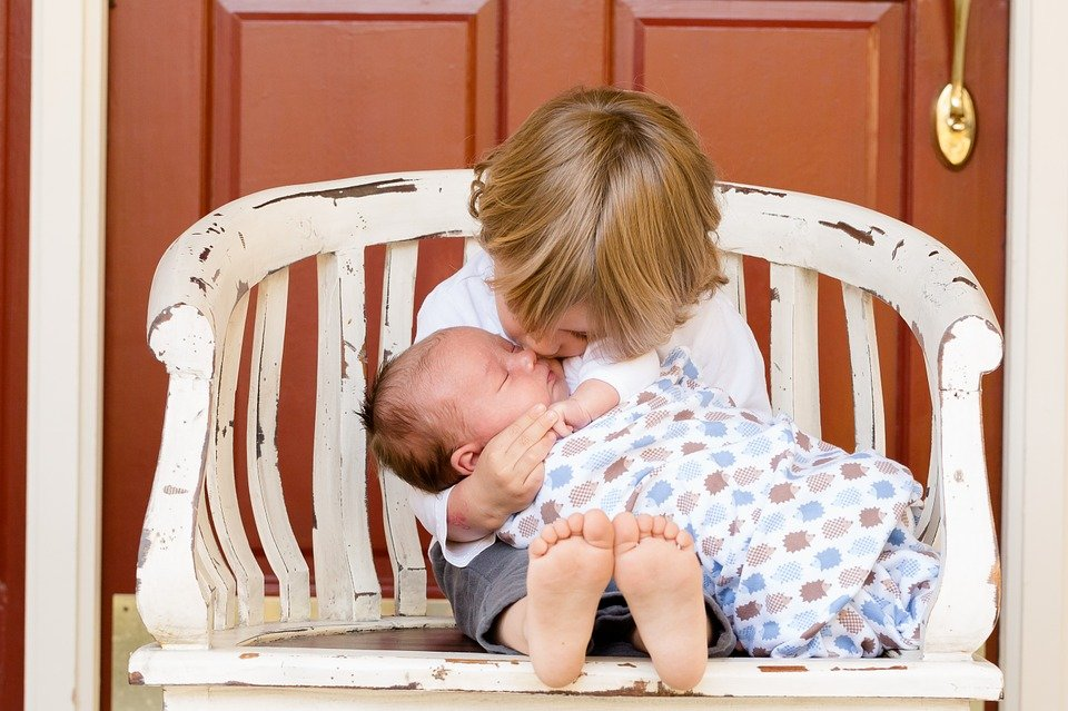 little boy holding and kissing baby