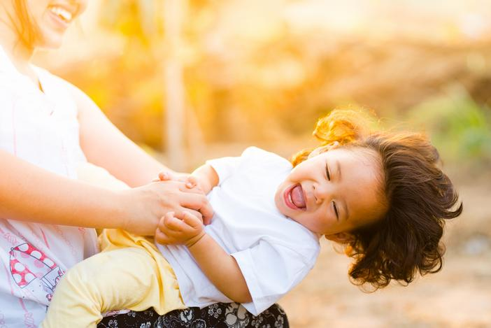 babysitter playing with a toddler both laughing