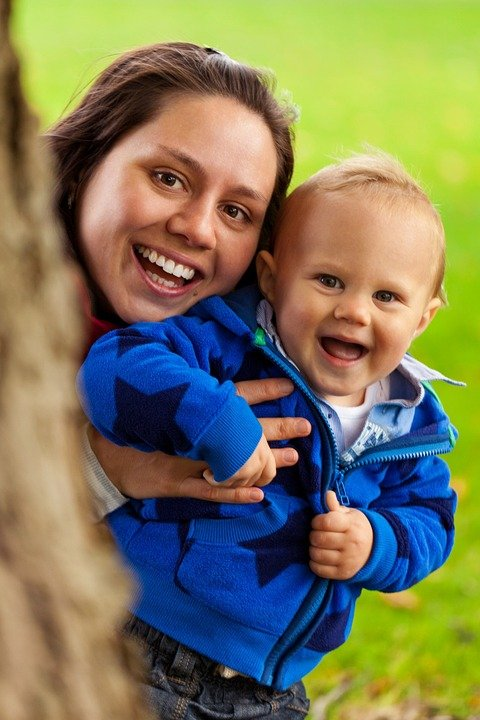 babysitter smiling with toddler heads close together