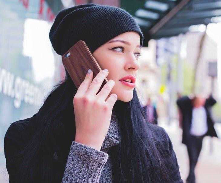 woman wearing black beanie on head talking on cellular phone