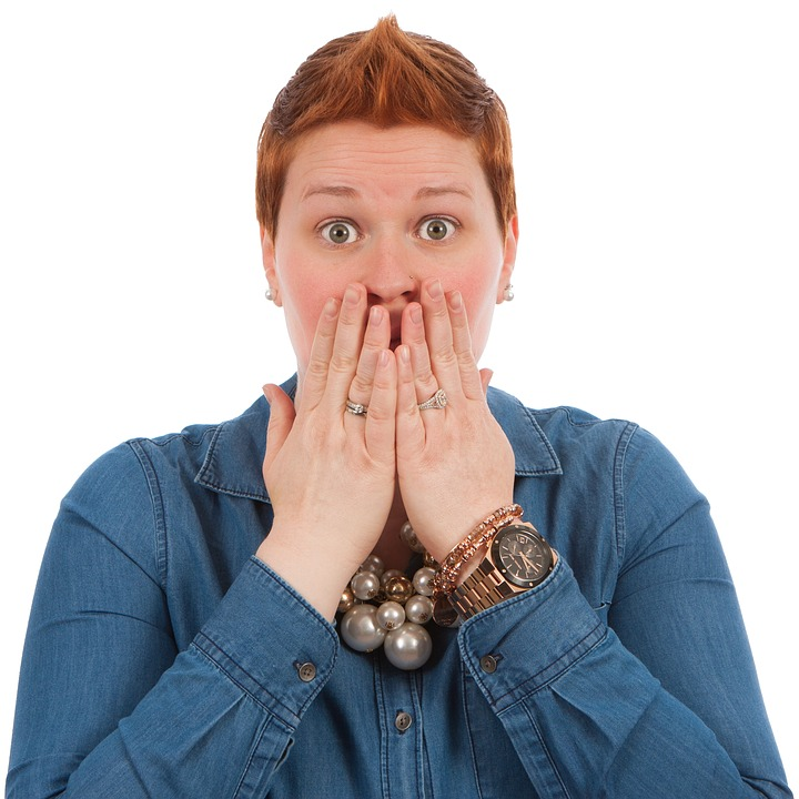 shocked expression on woman with short red hair, hands covering mouth