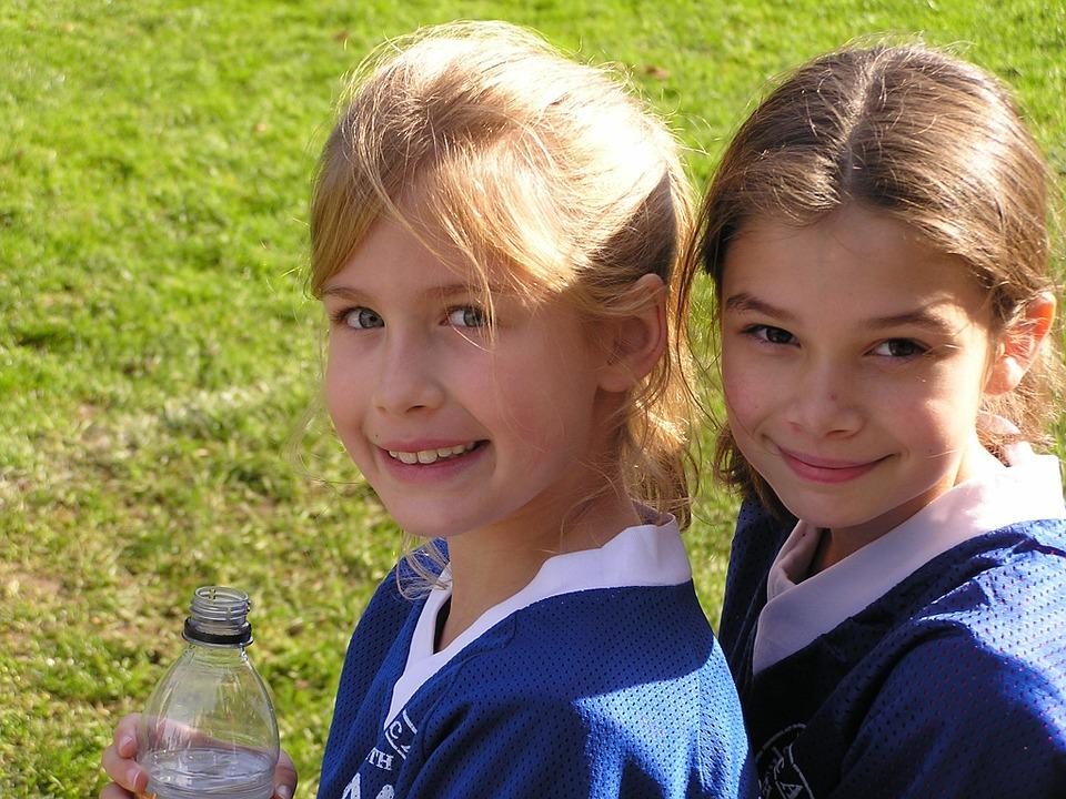 BFFs two girls in sports jerseys on a green field