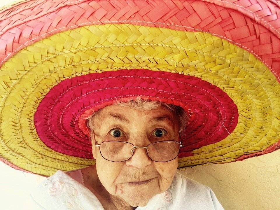 elderly woman trying on a colorful pink and yellow sombrero