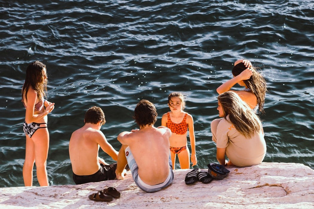 six children in swimsuits standing near the edge of a body of water sunny day.