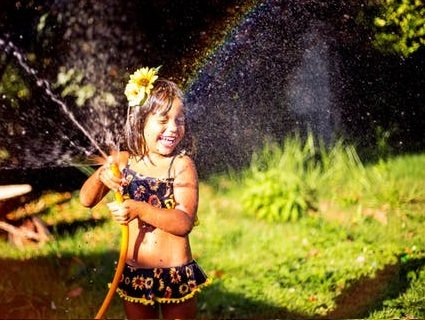 girl with yellow flower in hair and sunflower swimsuit laughing as water from hose sprays her face.