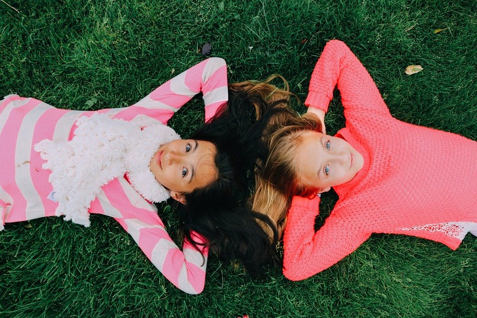 two girls lying on grass with heads together