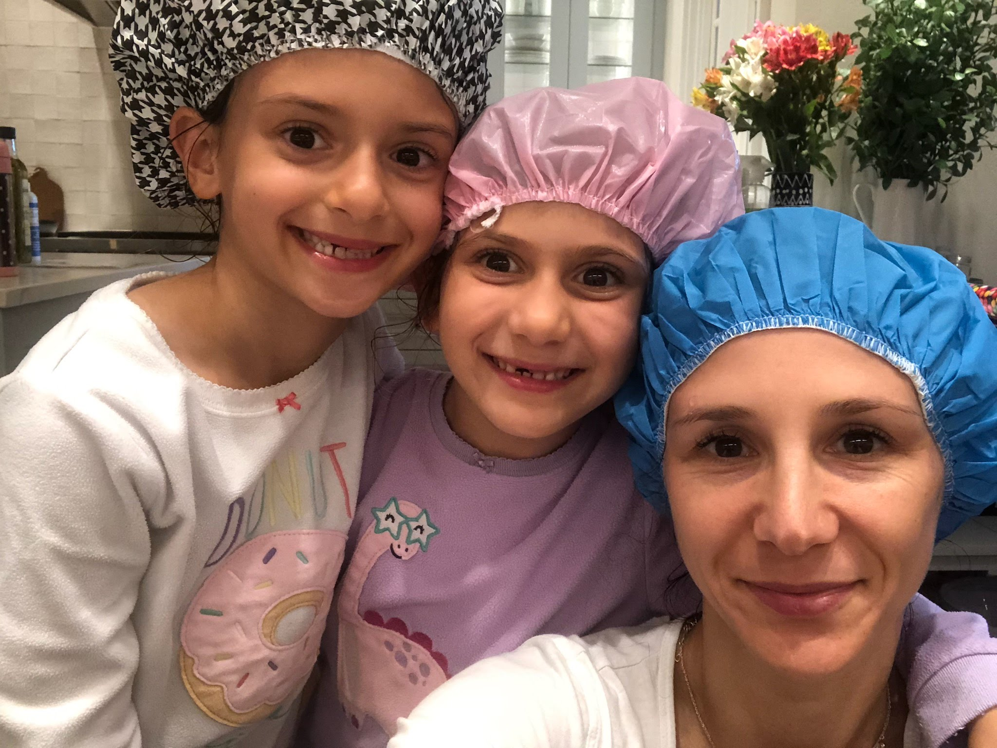 LiceDoctors Technician taking head-to-head selfie with two smiling little girls, all wearing shower caps