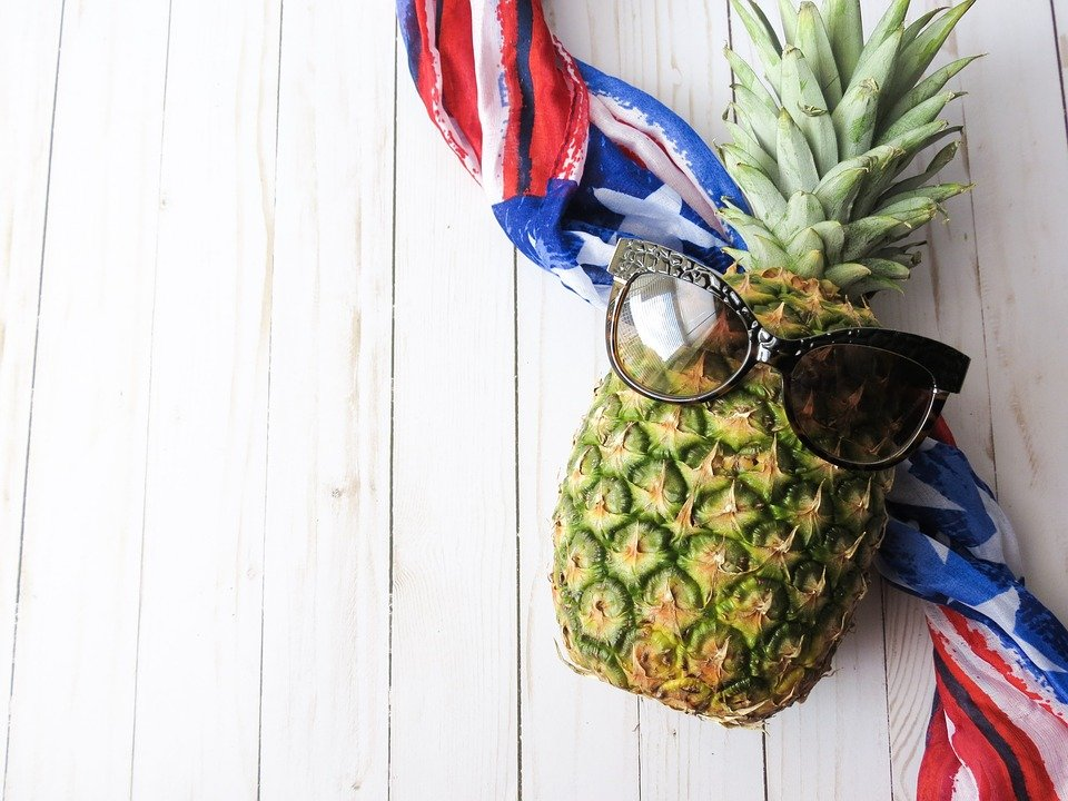 photo image evoking patriotism and celebration pineapple with sunglasses on a red-white-blue banner.