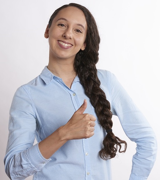 woman with long brown braid smiling broadly giving a thumbs-up hand sign.
