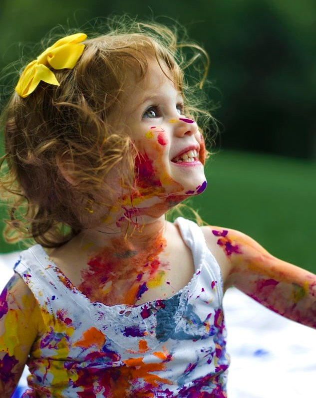 blonde toddler girl covered in messy paint on clothes and face.