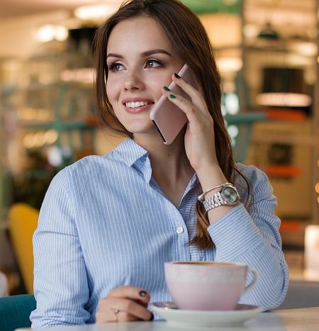 smiling woman talking on a cell phone in a coffee shop.