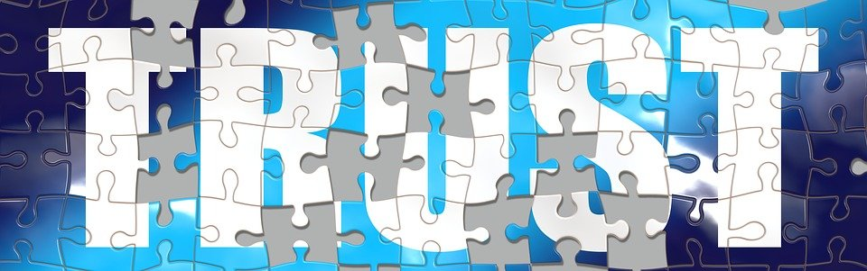 blue jigsaw puzzle with white letters TRUST.