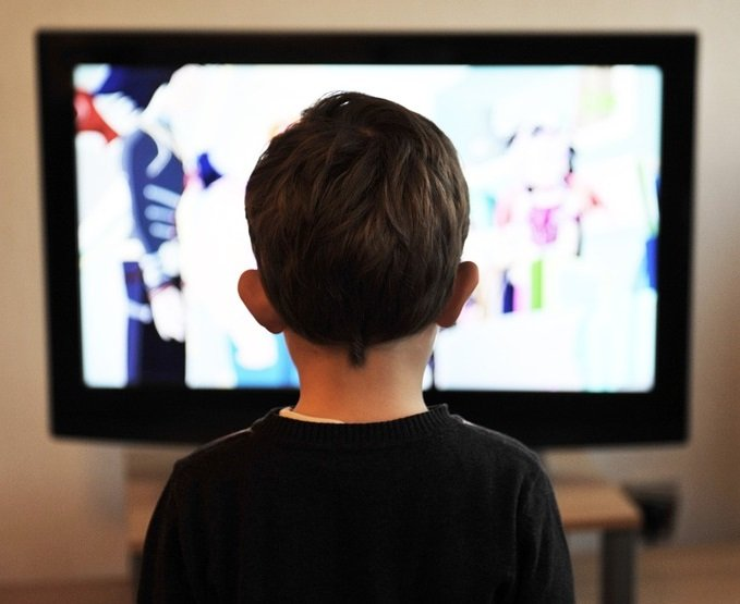 rear view of child watching tv, soft focus television in background
