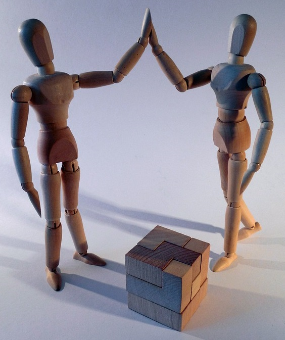 two wooden articulated puppets high-fiving over completed wooden block puzzle cube.