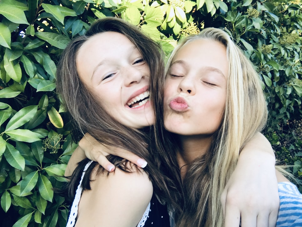 two long haired girls hugging and smiling and posing, heads close together for selfie.