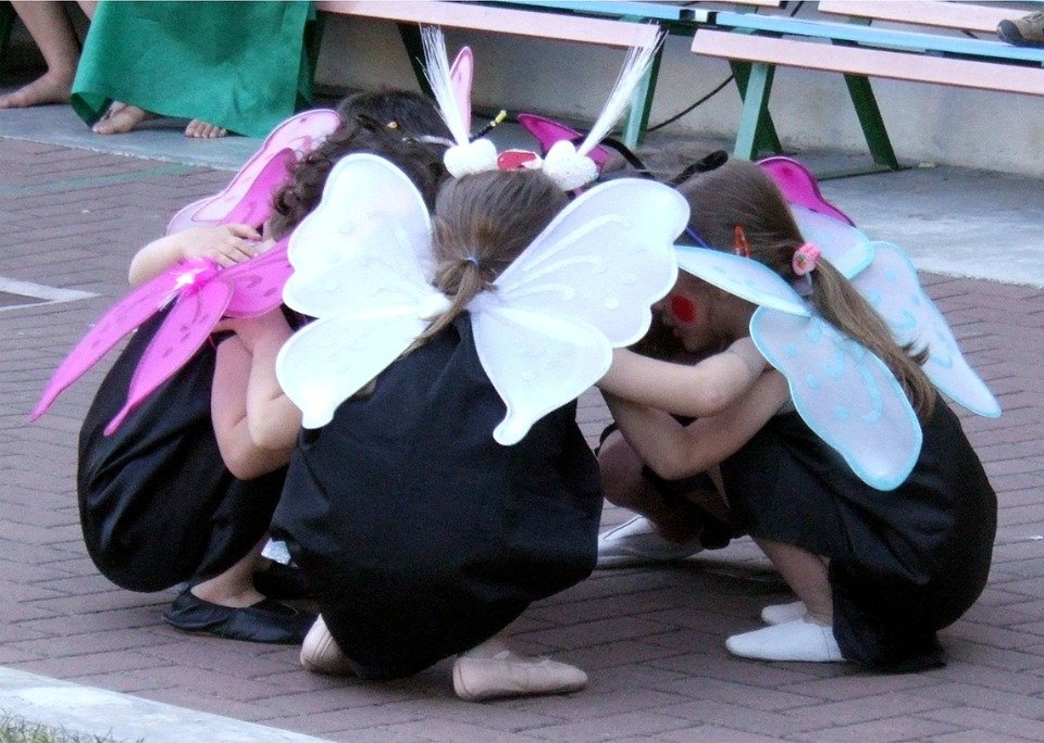 very young children wearing fairy wings and black costumes kneeling huddled together.