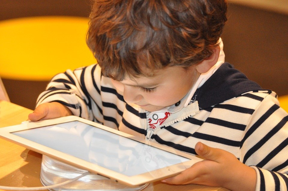 downward view of a young child looking at a tablet like an iPad.