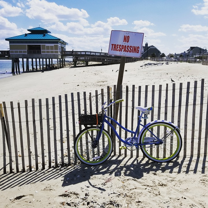 bicycle leaning against a fence next to a beach house and NO TRESPASSING sign.