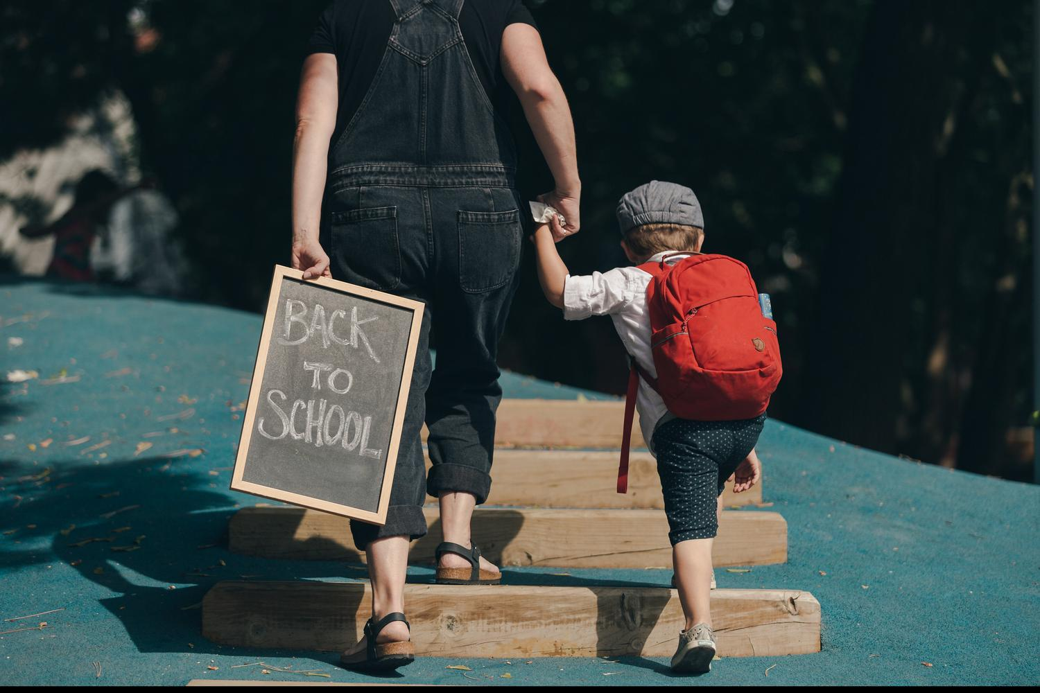 rear view of adult holding a Back To School chalkboard and the hand of a child wearing red backpack.