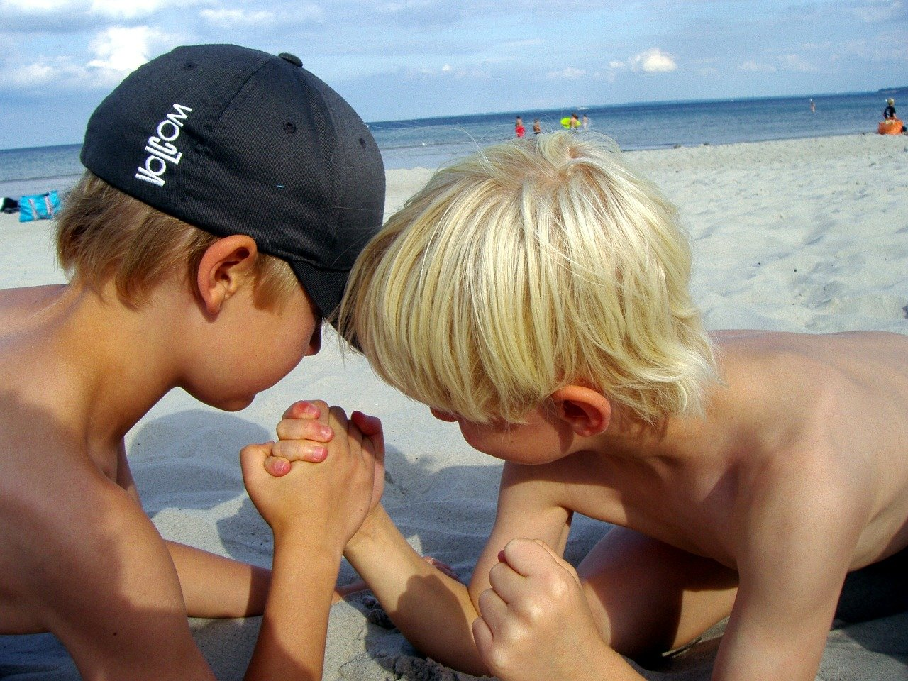 two boys arm wrestling in the sand at the beach, heads close together