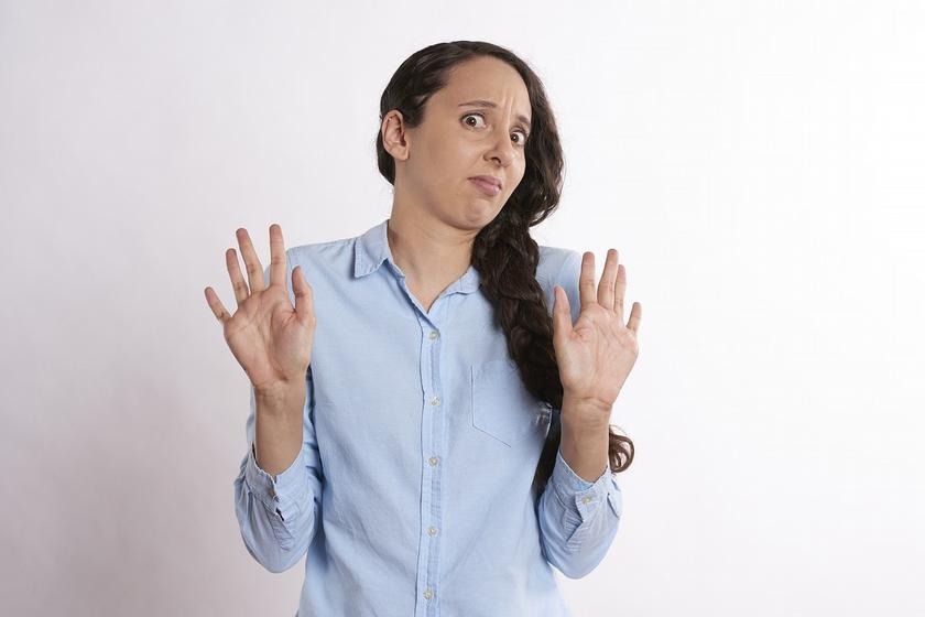 grimacing woman, holding hands up to signal disgust no thank you