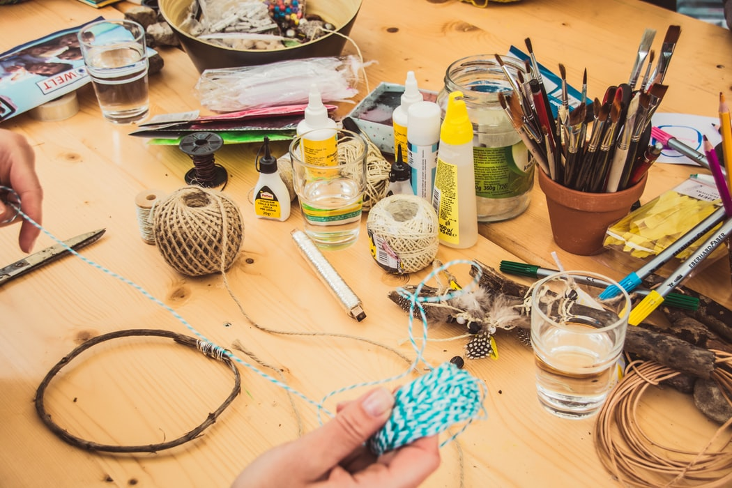 craft workbench assorted supplies, glue, twine, spools, scissors, hand holding string and twig.jpg