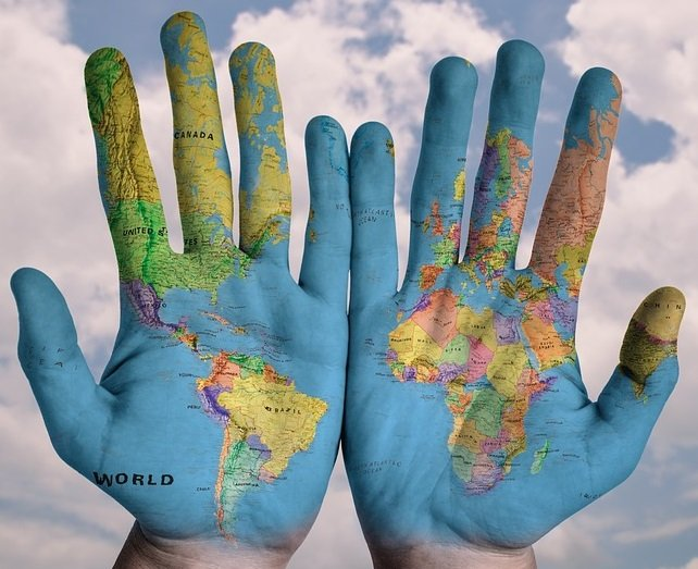 two hands spread painted with image of world map showing Americas and Europe and Africa.