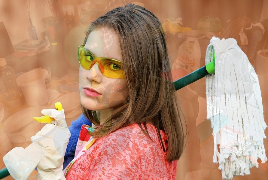 woman holding mop and cleaning supplies wearing rubber gloves and glasses