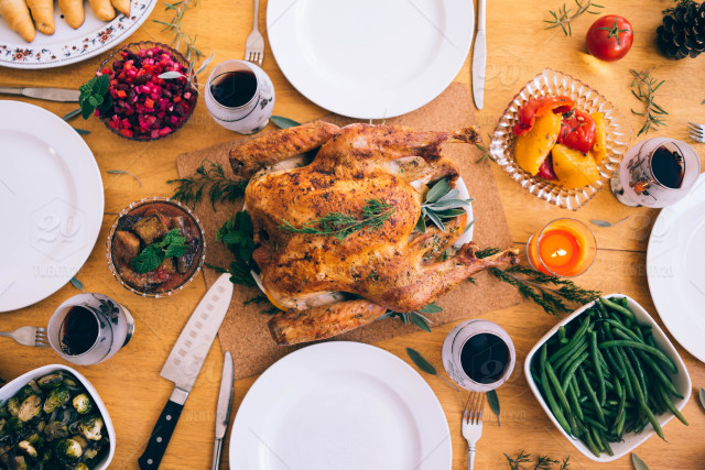 Overhead view of dinner table with turkey, side dishes, plates, cutlery, wine glasses
